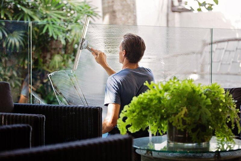 personne nettoyant une vitre sans robot nettoyeur de vitre