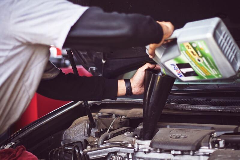 un mécanicien remplissant une voiture d'huile 10w40