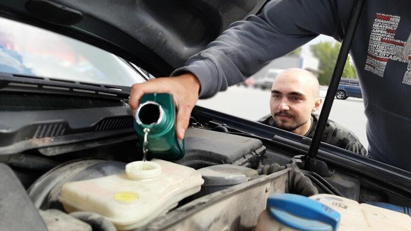 garagiste versant huile de transmission dans un moteur