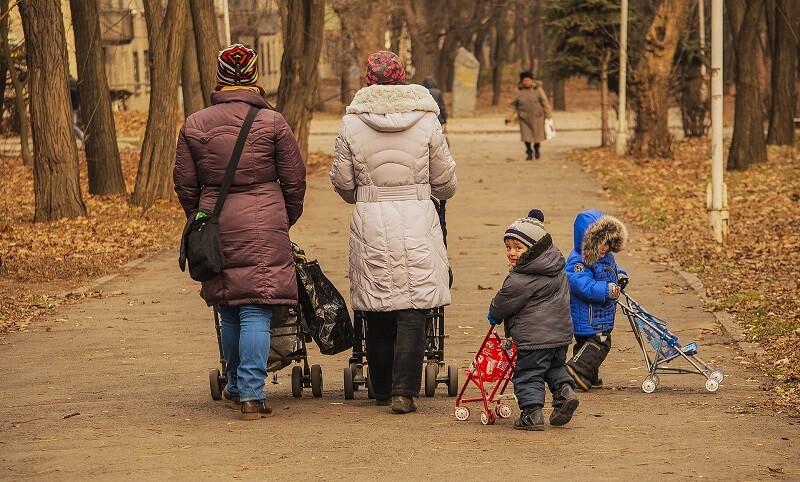 Deux mamans et leurs enfant avec des poussettes dans un parc