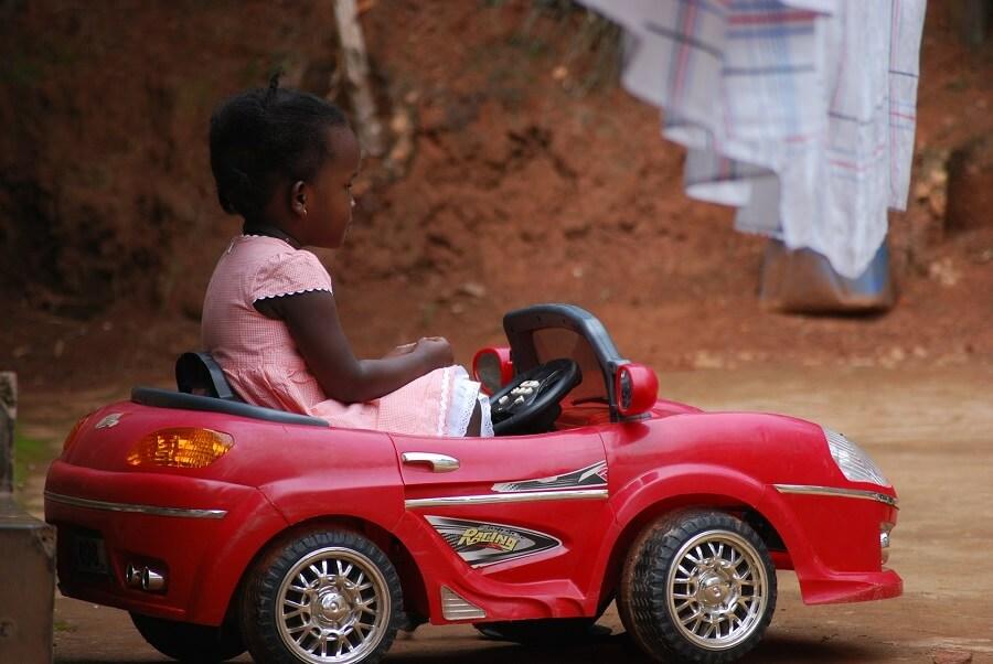 Un enfant dans une voiture jouet rouge pose sur une route en terre