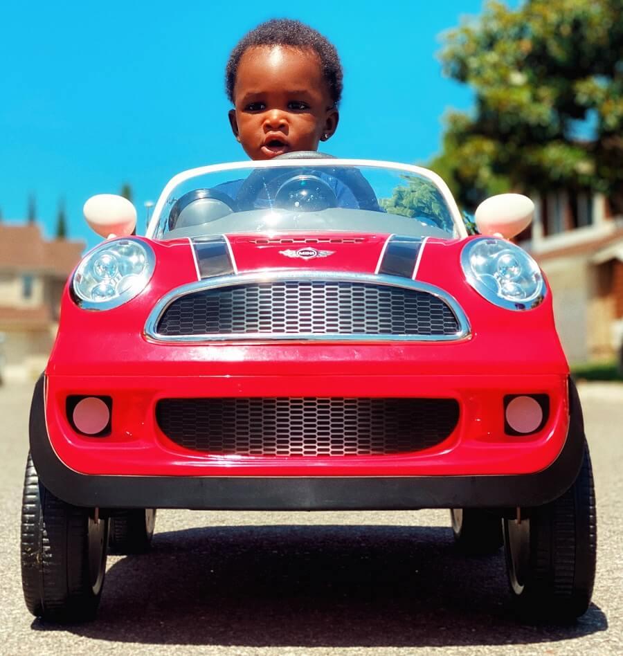 Une image en milieu urbain montre une voiture électrique pour enfant, pleine de lumières