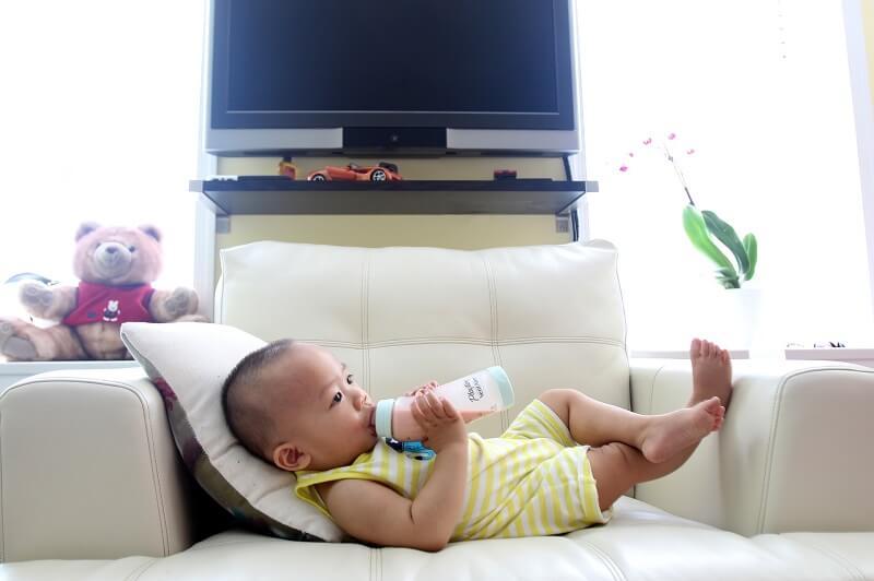 bébé coché sur un fauteuil buvant son biberon