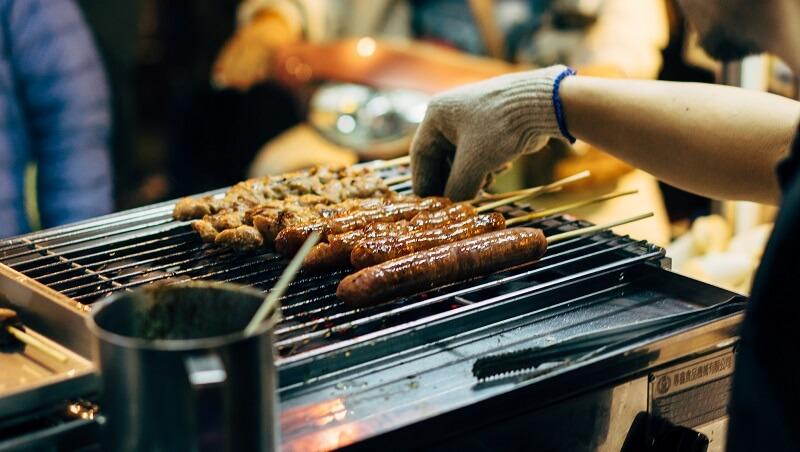 Photo de personnes dans une zone extérieure préparant des aliments au grill.