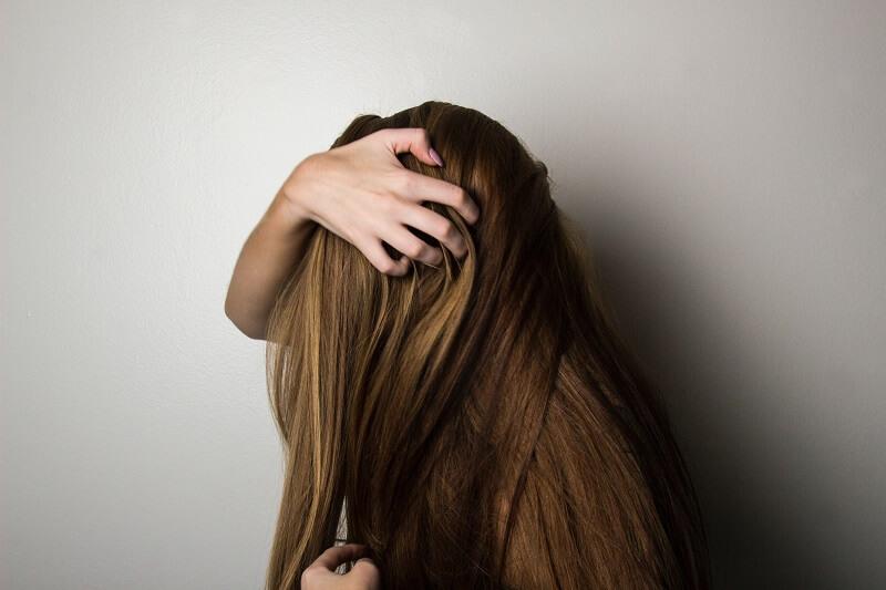 Une femme passe un produit sur les cheveux