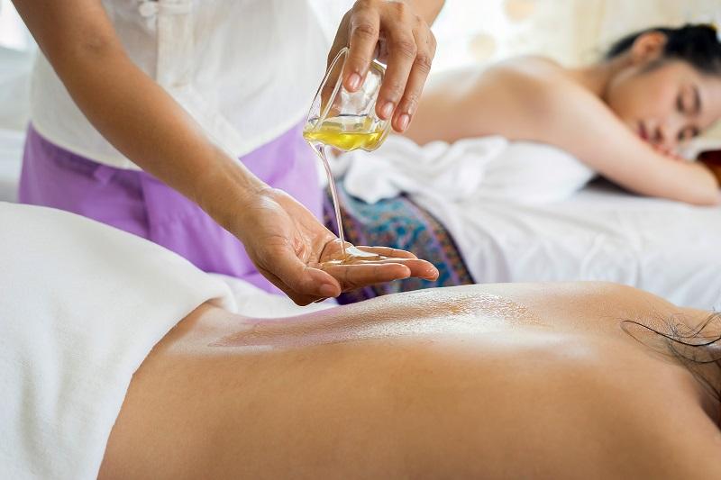 En donnant des massages.