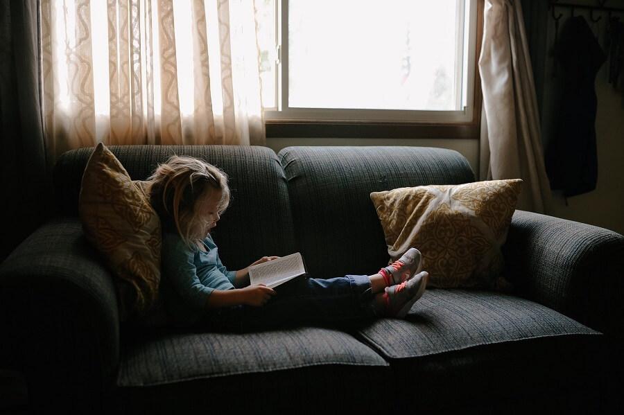 Un enfant faisant la lecture sur le sofa