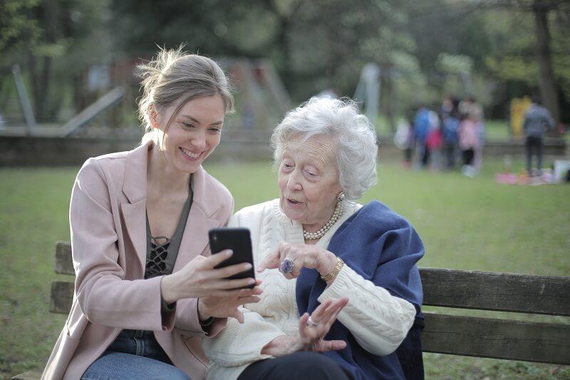 Image d'un 'une mère et sa fille manipulant un téléphone portable.