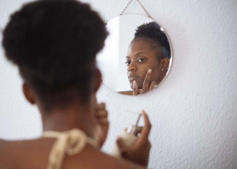Femme se mettant de la crème anti cerne