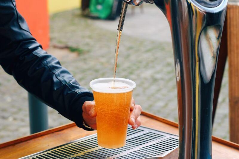 L'image montre un verre de bière devant un homme qui fait un signe positif.