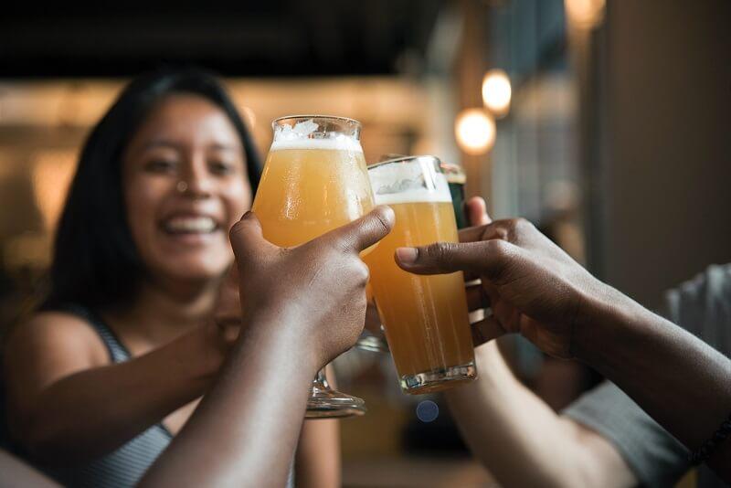 L'image montre un groupe d'amis en train de trinquer à la bière.